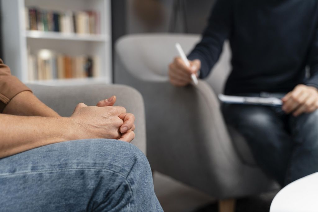 woman-holding-hands-together-talking-with-counselor.jpg
